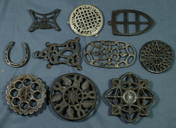 3: Lot of 10 cast iron trivets, various shapes, largest