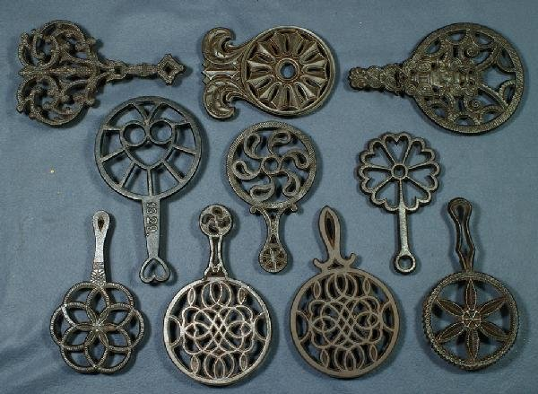 6: Lot of 10 handled cast iron trivets, longest 11""