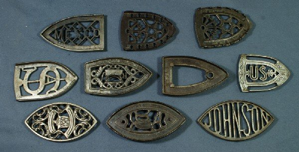 12: Lot of 10 handleless cast iron trivets, 8 signed, l