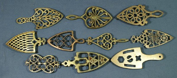 13: Lot of 9 handled brass trivets and one handleless b