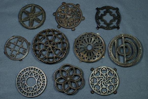 19: Lot of 9 round handleless cast iron trivets and one