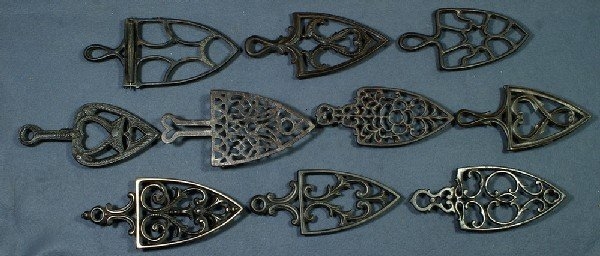 "20: Lot of 10 handled cast iron trivets, longest 9 1/4"""