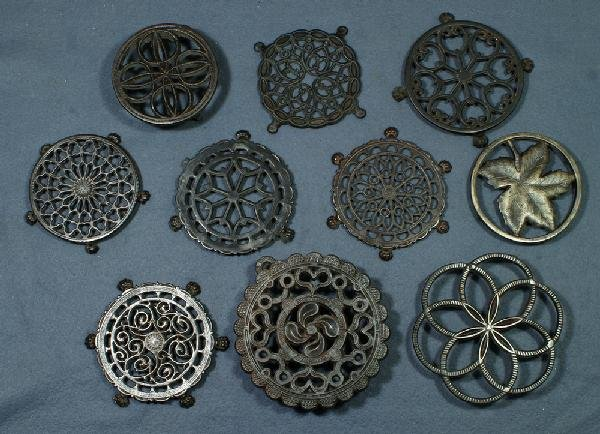 "21: Lot of 10 round cast iron trivets, largest 7 1/4"" d"