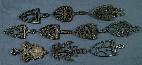 22: Lot of 10 handled cast iron trivets, longest 9""