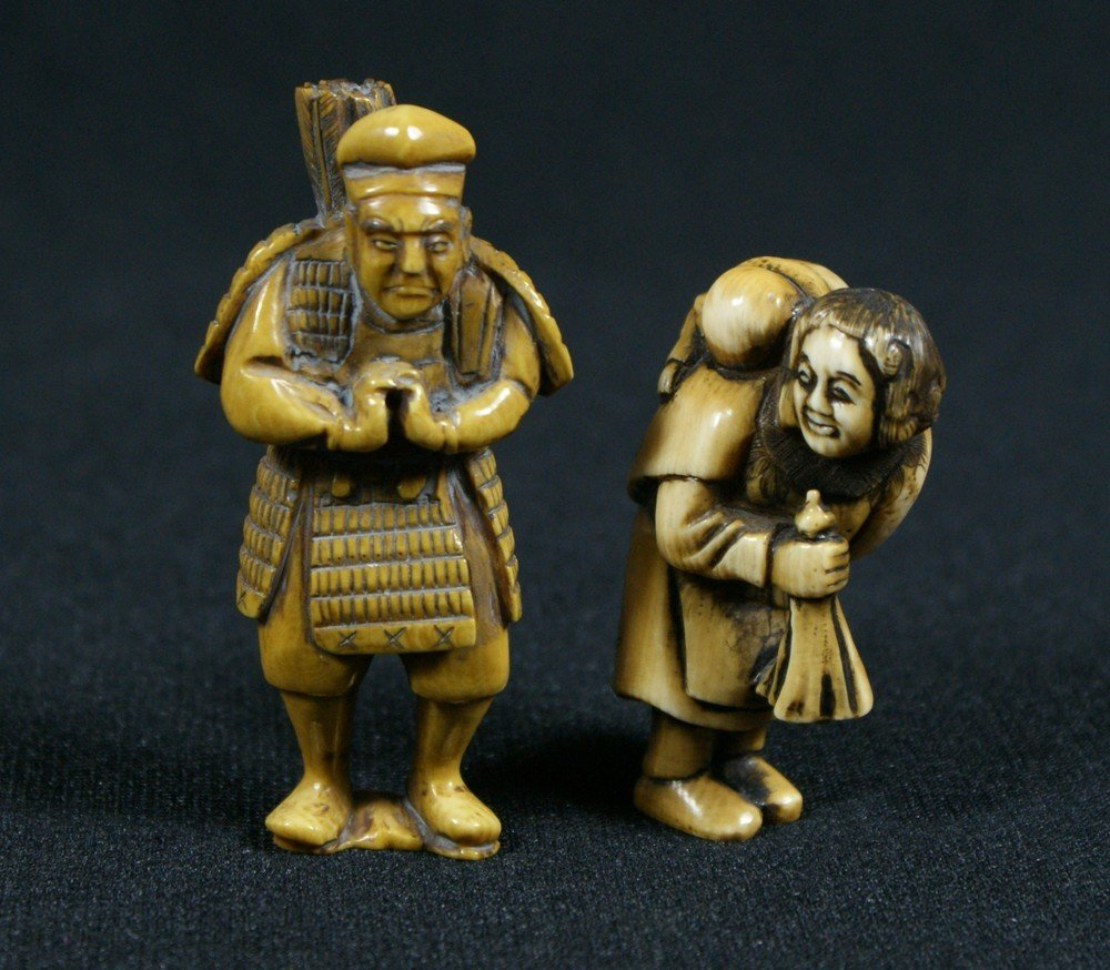 2137E: 2 carved ivory netsuke, standing archer, woman w