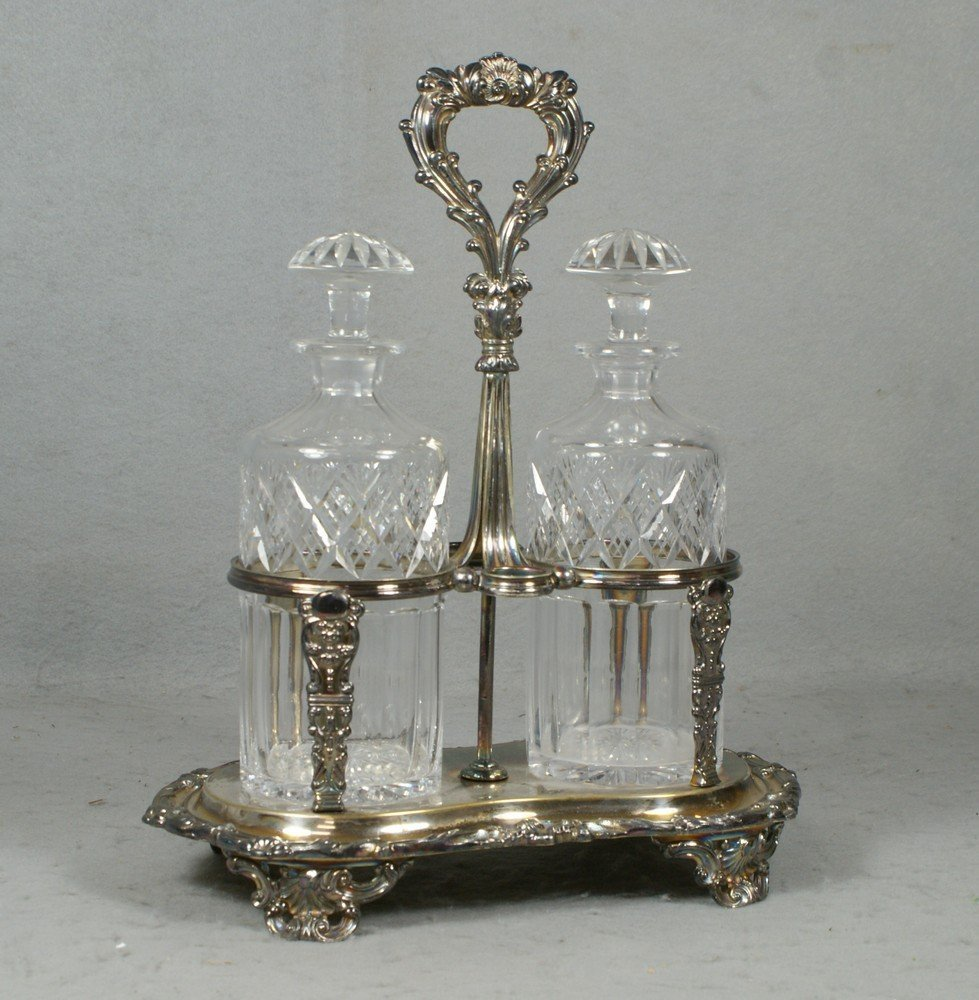 4026: Plated silver decanter stand, 2 cut crystal bottl