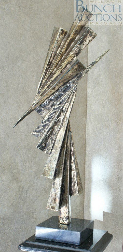 24: Unsigned abstract metal sculpture on a gray marble