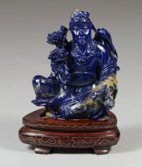 Carved Obsidian Figure Of A Seated Man Holding Flowers