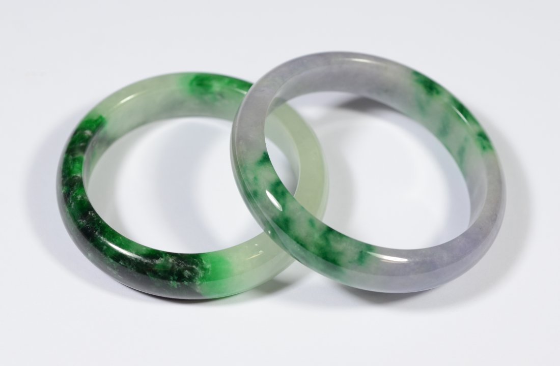 Two (2) Chinese carved jade bracelets, one with touches