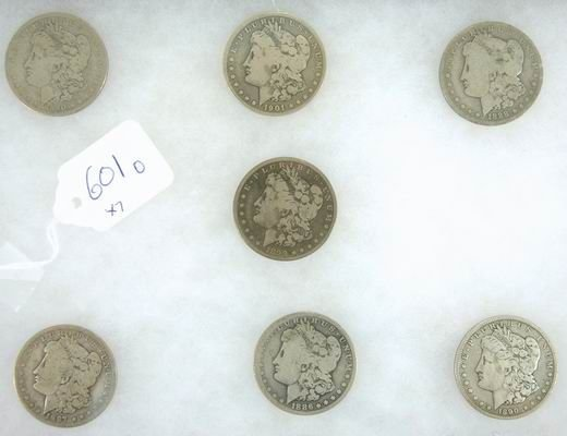601O: LOT OF 7 MORGAN SILVER DOLLARS