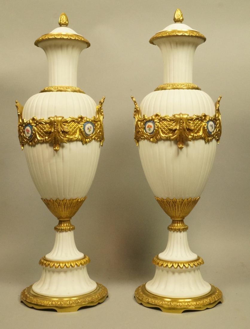 Pr White Porcelain Bisque Urns. Gilt metal mounts