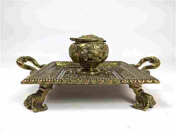 Fancy Brass Footed Inkwell. Single inkwell with faces.
