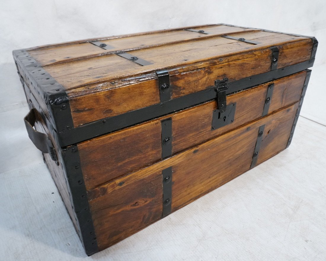 Antique wooden chest. Black metal straps. Leather