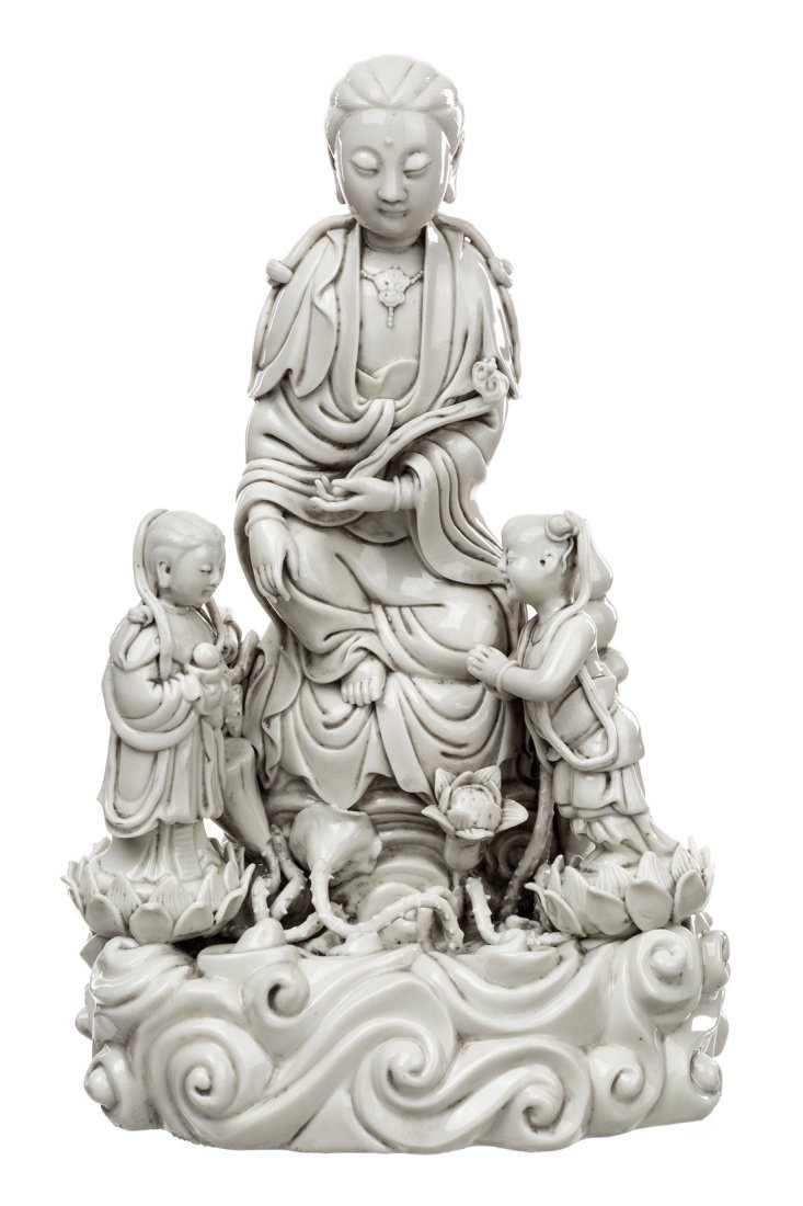 A BLANC-DE-CHINE FIGURE OF GUANYIN ON A ROCK WITH TWO