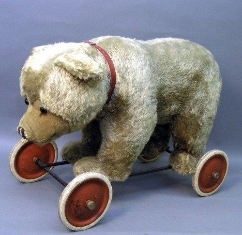 26: A Steiff Teddy bear on wheels, 26in. long