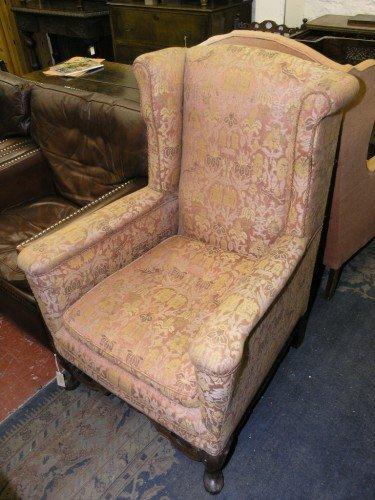 1089: A Georgian design walnut wingback armchair,