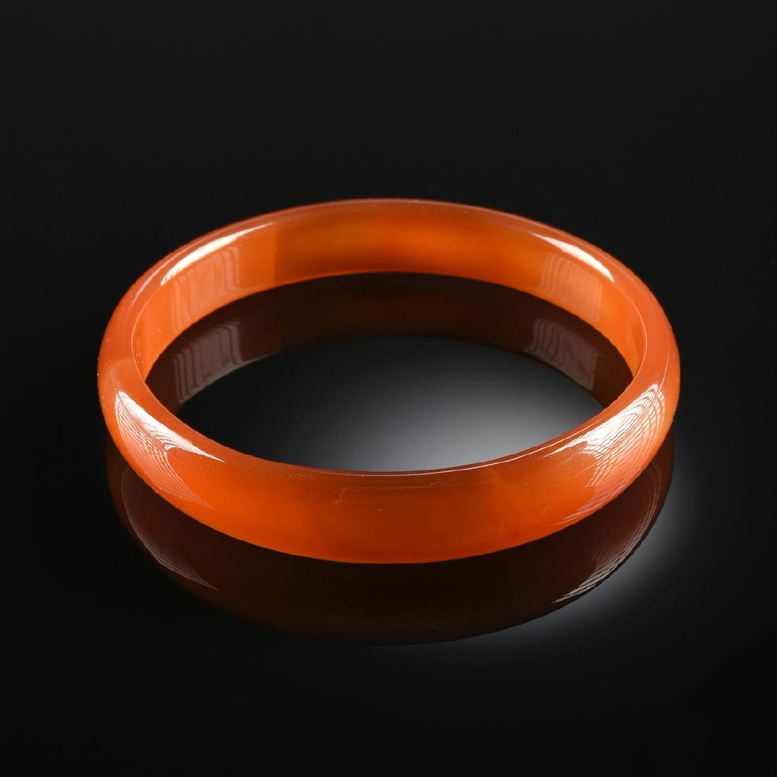 AN ORANGE AND YELLOW AGATE LADY'S BANGLE,