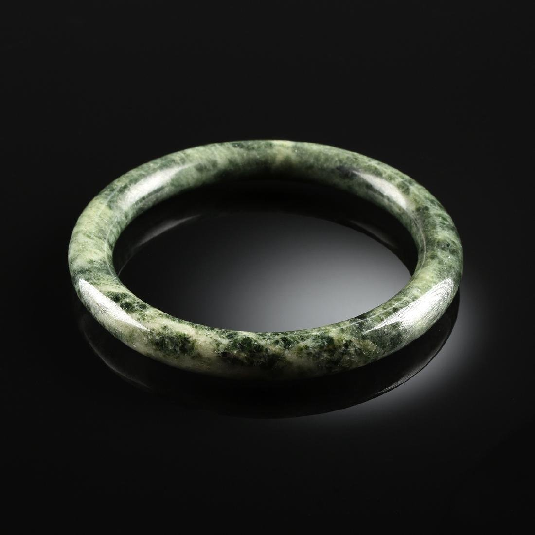 A SPINACH GREEN JADE LADY'S BANGLE,