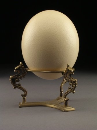 7: AN OSTRICH EGG SHELL supported by a circular brass t