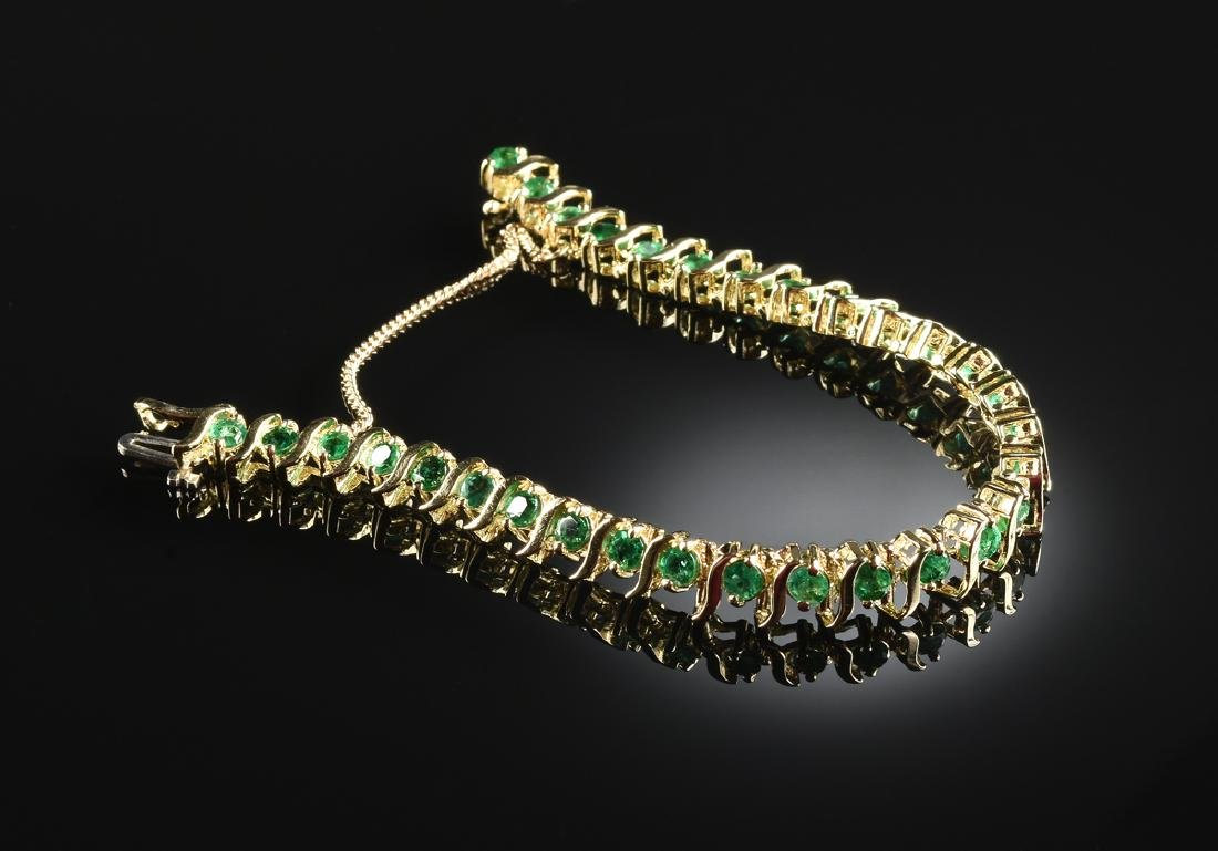 "A 14K YELLOW GOLD AND EMERALD ""S"" LINK LADY'S TENNIS"