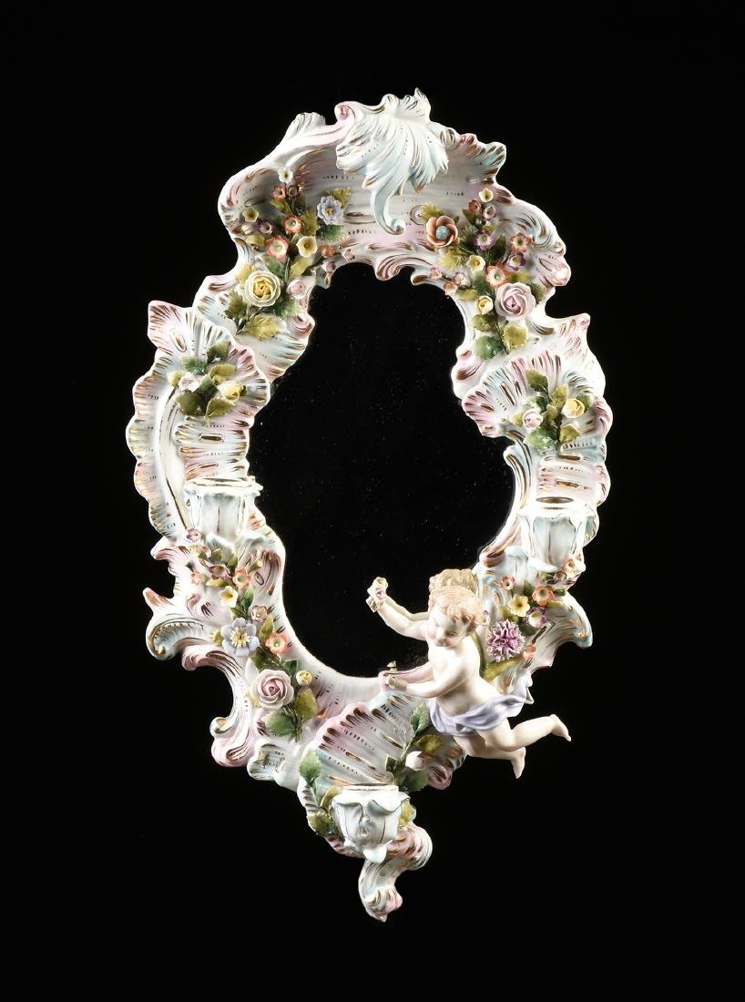 A GERMAN PAINTED AND FLORAL ENCRUSTED PORCELAIN MIRROR