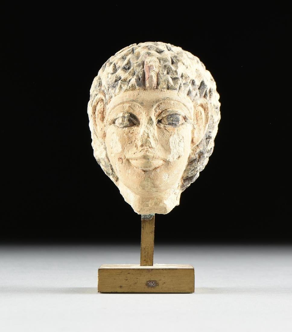 AN ANCIENT EGYPTIAN CARVED AND PAINTED LIMESTONE