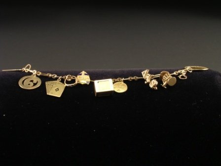 16: A GOLD CHARM BRACELET, the link chain suspending te