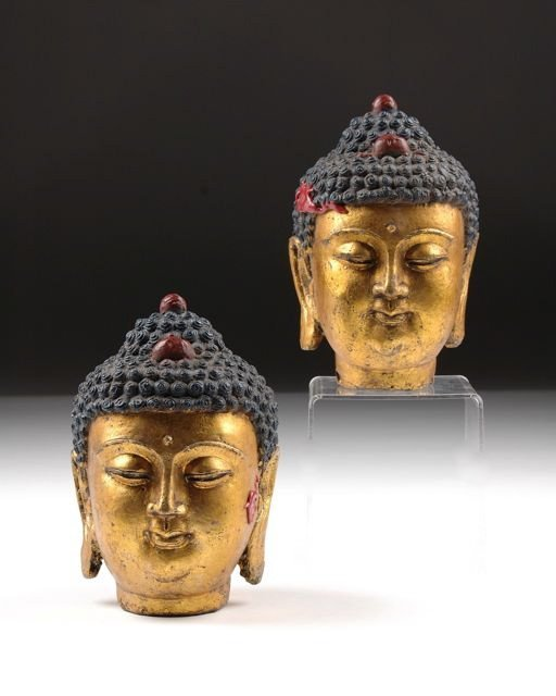317: A PAIR OF CHINESE PARCEL GILT CAST IRON HEADS OF B