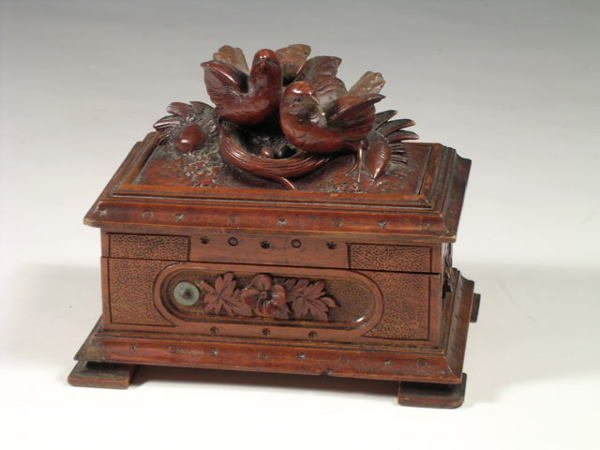 6: An antique music box encased within a carved black f