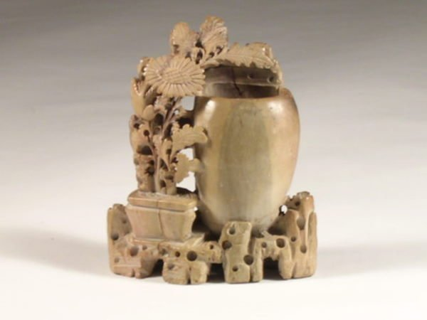 7: A Chinese carved steatite vase modeled with flowerin