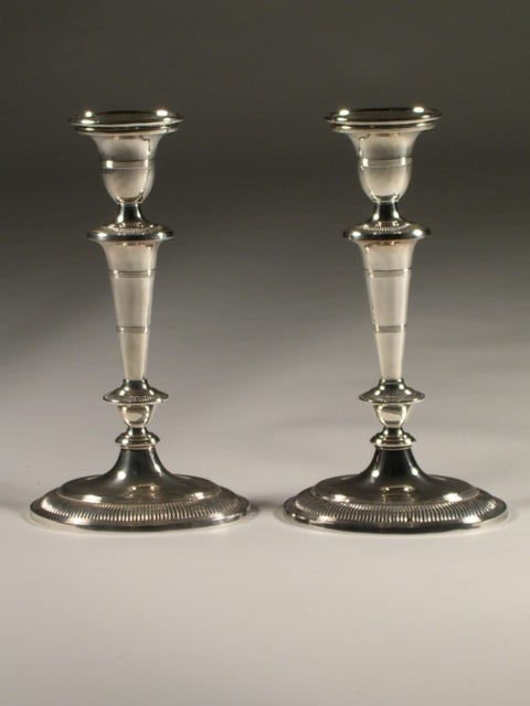 22: A pair of silver plated candlesticks, each on oval