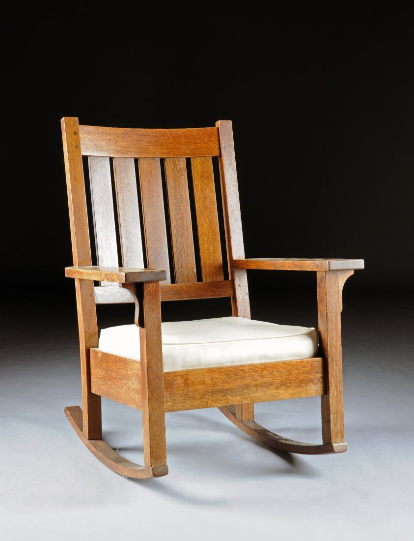 373:  AN ARTS AND CRAFTS CARVED OAK ROCKING CHAIR, BY G