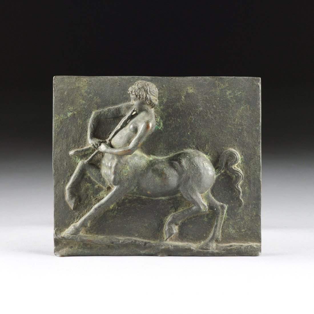 A CONTINENTAL PATINATED BRONZE PLAQUE OF A CENTAUR