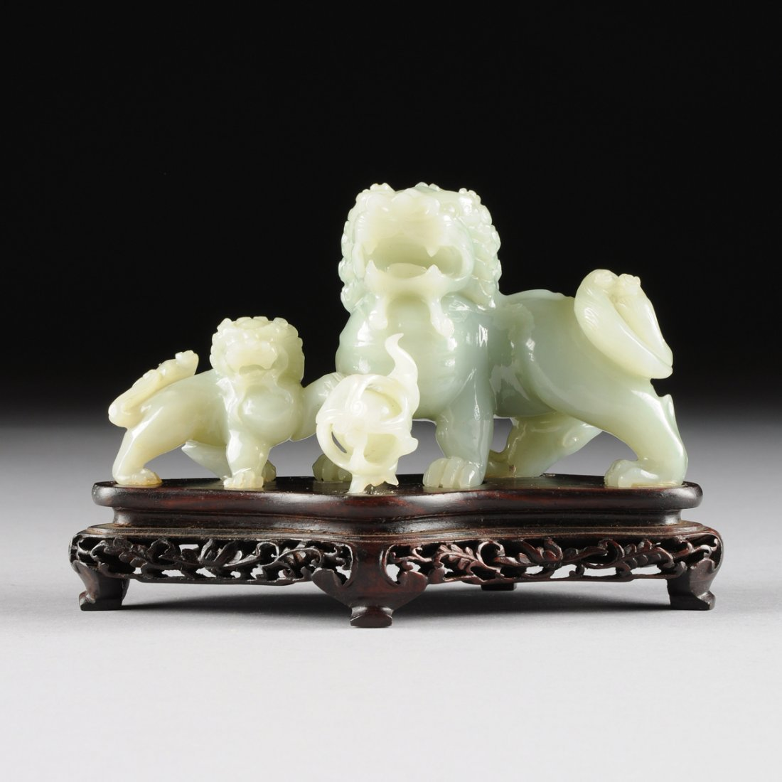A CHINESE CARVED JADEITE FIGURAL GROUP OF TWO FOO DOGS,