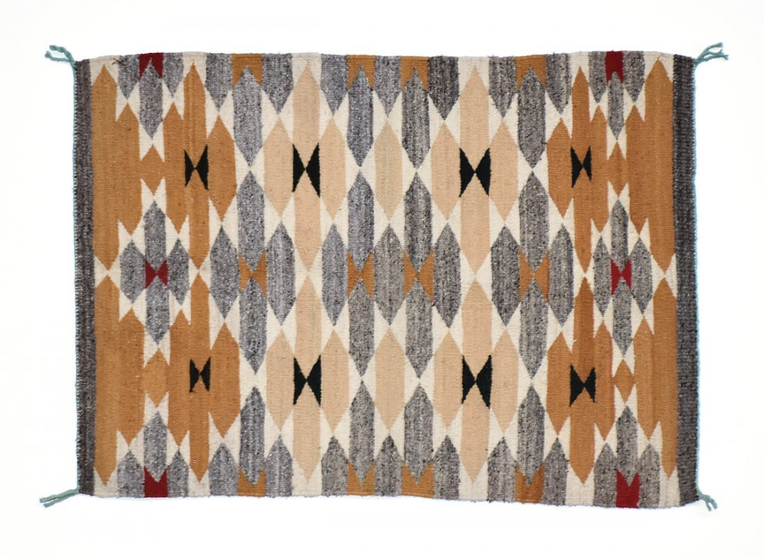 A SMALL NATIVE AMERICAN OCHRE GROUND WOVEN WOOL RUG,