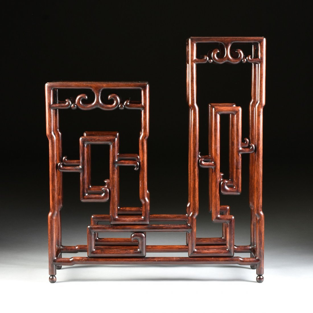 A CHINESE CARVED HARDWOOD STEPPED PEDESTAL FORM STAND,
