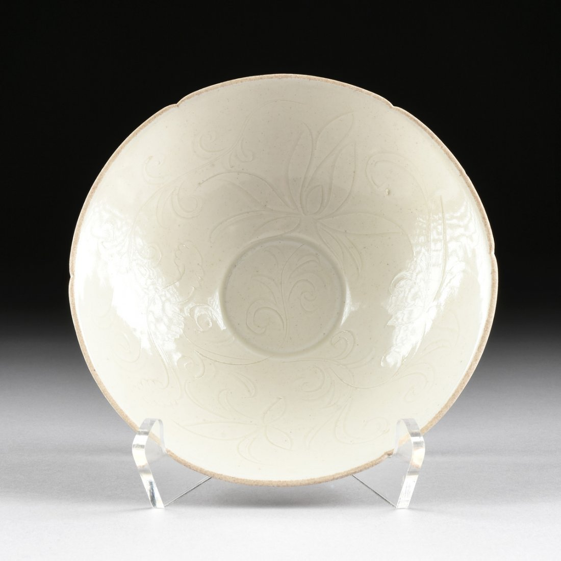 A CHINESE INCISED AND WHITE GLAZED SHALLOW BOWL,