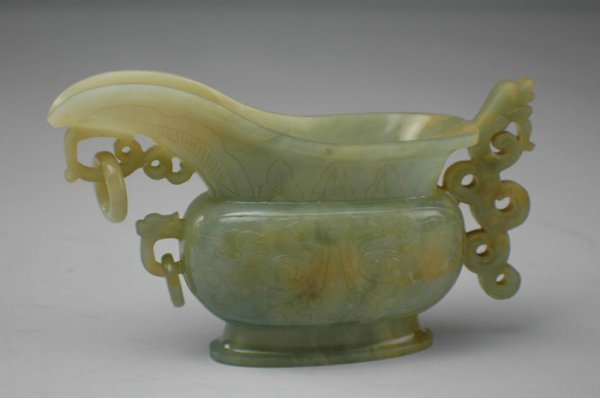 13: A CHINESE CARVED JADE PITCHER, on conforming base,