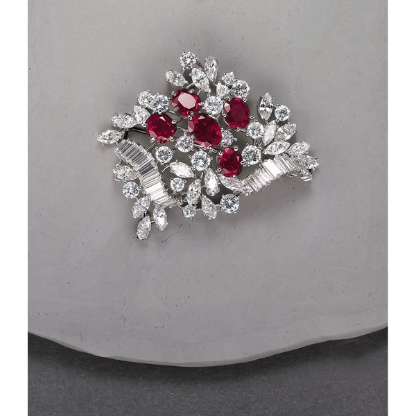 17:        A Ruby and Diamond Brooch  Of foliate scroll