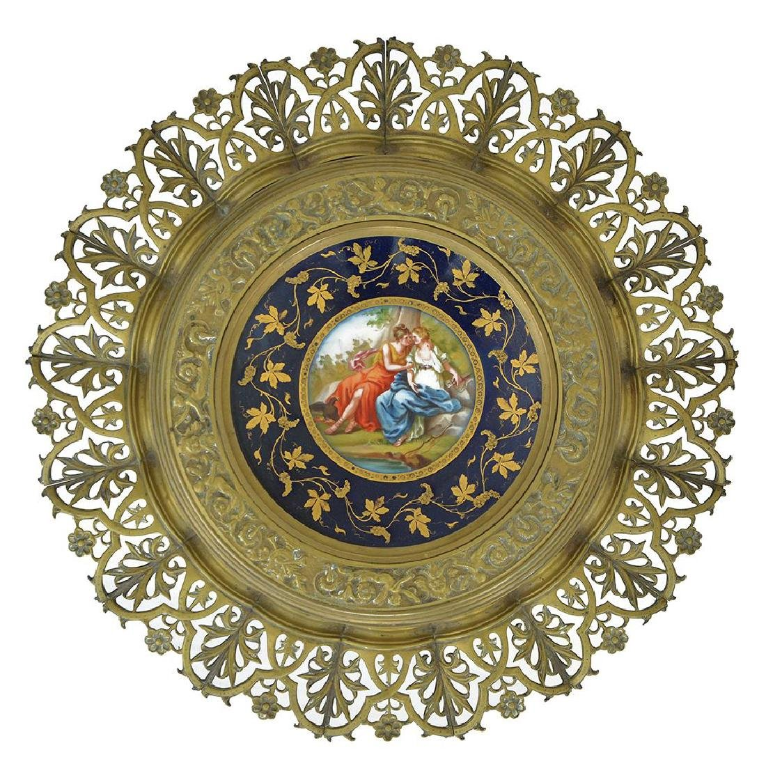 A BRASS TAZZA MOUNTED WITH A PORCELAIN PLATE