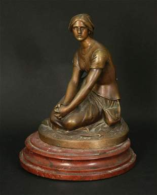 A BRONZE SCULPTURE OF A YOUNG WOMAN