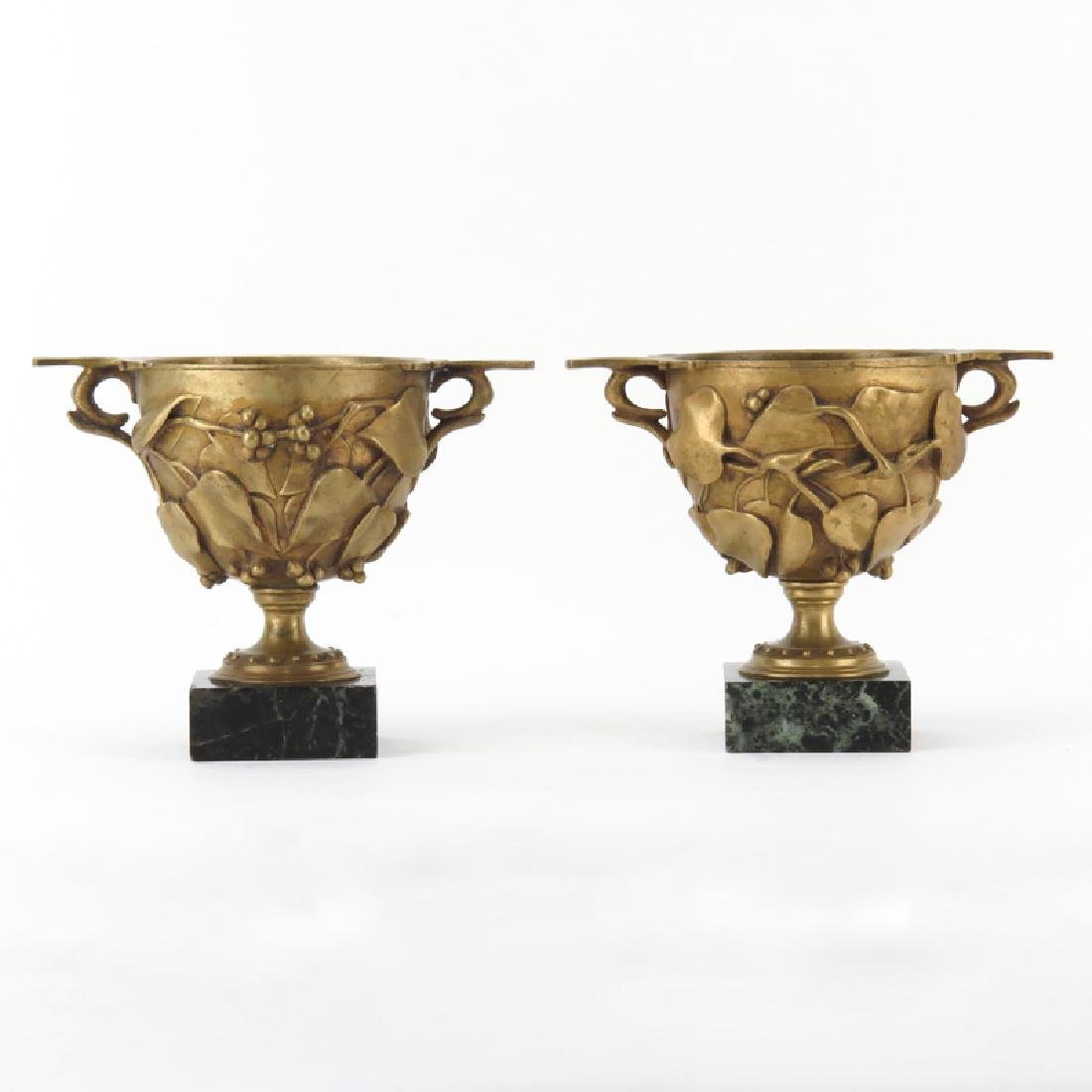 Pair of French Early 20th Bronze Urns on Marble Base.