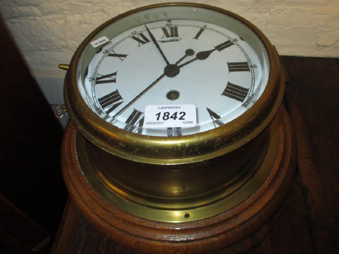 Oak and brass ship's bulk head clock, the enamel dial