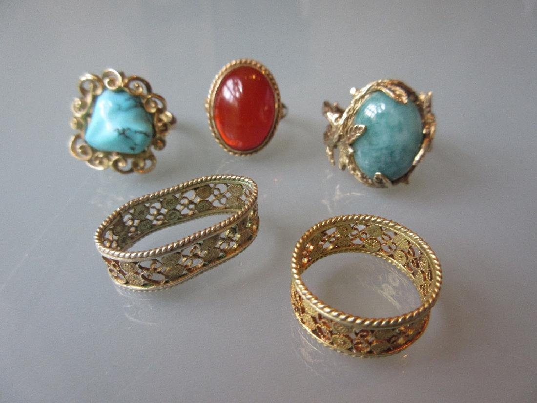 Three various gold dress rings together with two