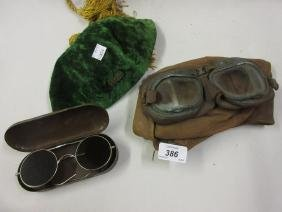 Pair of leather and glass goggles, leather hat, green