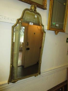 Shaped gilt framed wall mirror with shell surmount and