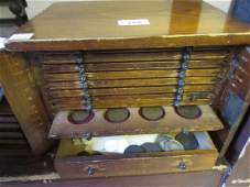 Stained pine coin collectors cabinet containing a