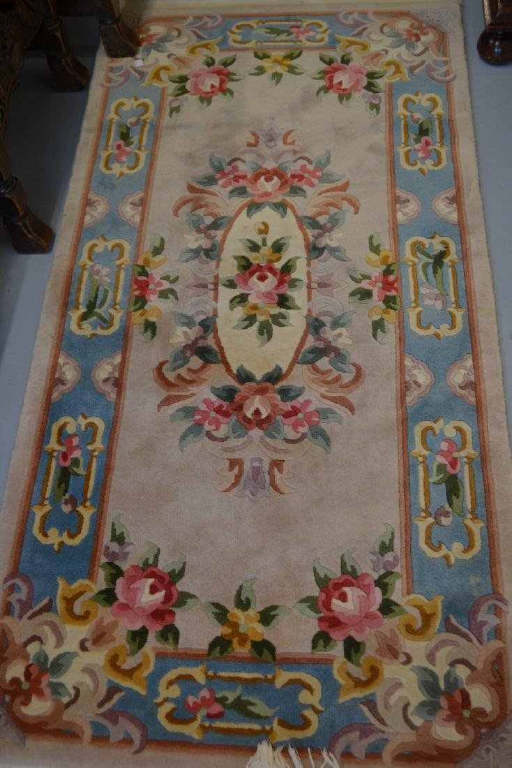Small Chinese rug with beige ground together with a