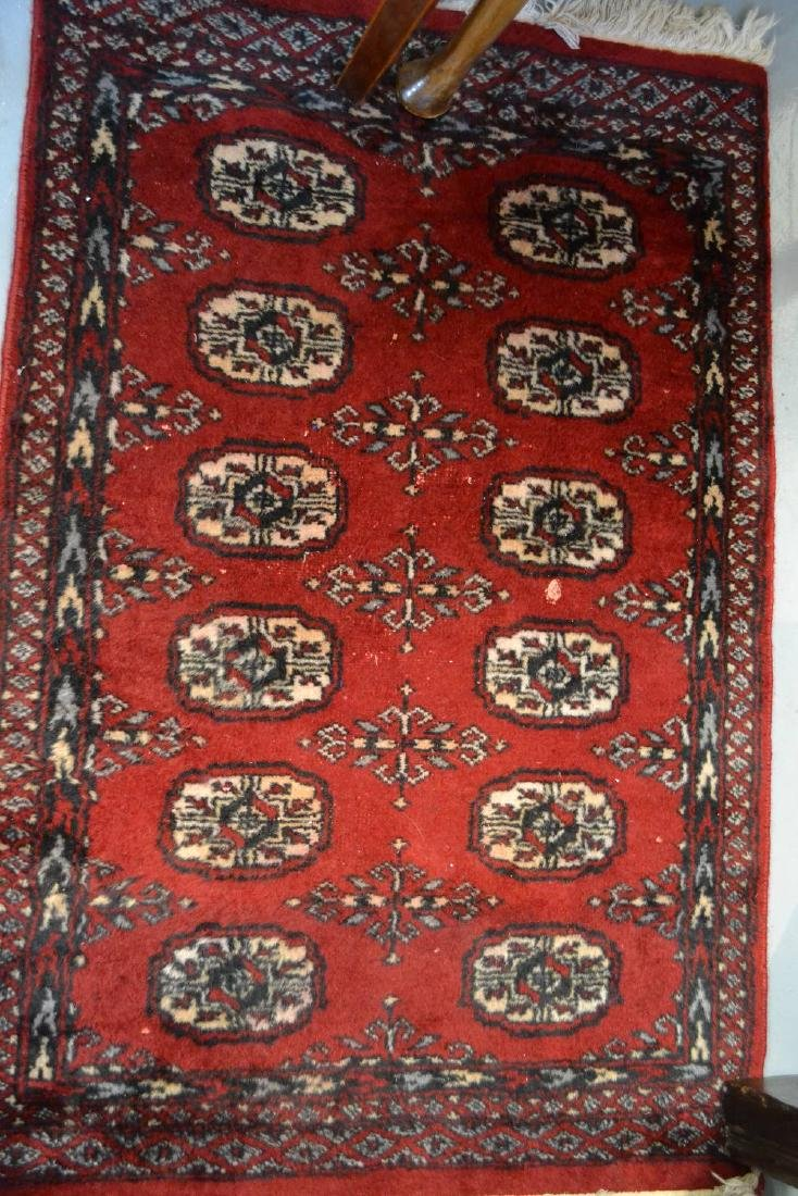 Small handmade rug having multiple gol design on a red