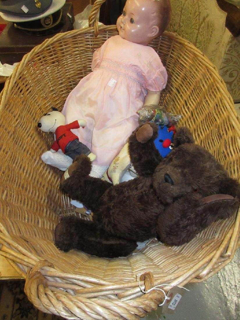 Wicker linen basket containing a composition doll,